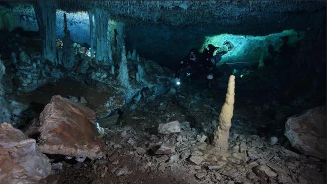 باستخدام مصباح يدوي فقط، يستكشف غواص من مركز أبحاث أنظمة المياه الجوفية لولاية كينتانا رو «سينداك» منجم مغرة قديم منذ نهاية العصر الجليدي الأخير. كانت هذه الكهوف جافة ومظلمة تمامًا. (الصورة لـ: © CINDAQ.ORG)
